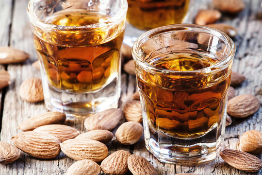 Italian amaretto liqueur with dry almonds on the old wooden back