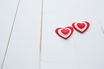 Two hearts hanging on white painted wooden background