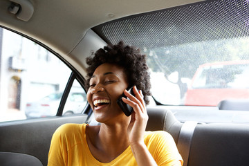 Laughing young woman in a car talking on mobile phone Wall mural