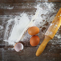 Cooking background with eggs, eggshells, flour and rolling pin.