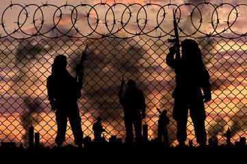 Silhouette terrorists near the border fence