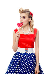 young woman eating colourful lollipop, dressed in pin-up style