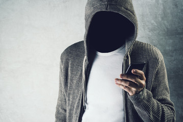Faceless hooded person using mobile phone, identity theft concep - fototapety na wymiar