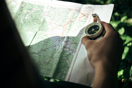 traveler exploring map with compass in sunny forest in the mount