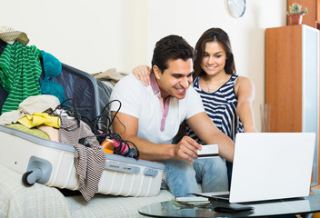 adults sitting near laptop and luggage