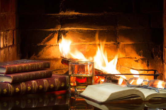 Glass of alcoholic drink and antique books in front of warm fireplace. Magical relaxed cozy atmosphere near fire