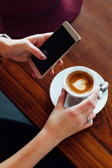 Woman using her smart phone in a cafe