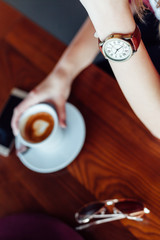 Woman in a cafe with watch in closeup