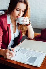 Woman drinking coffee and signing a document in a cafe