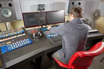 Sound studio technician preparing all settings on the mixing des