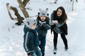 Happy young hipster family having fun, bowl, rising up, piggyback ride their children and relax in park on winter sunset