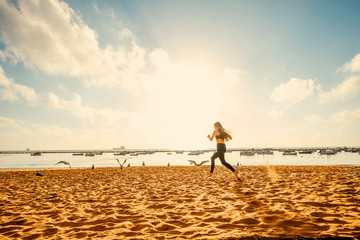 Woman running on the sandy beach