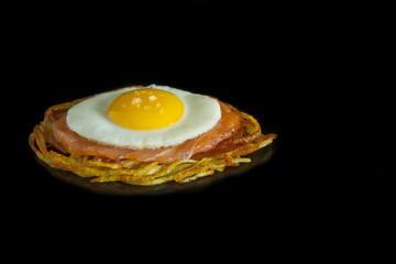Gerecht bestaande uit aardappelen, gerookte zalm en gebakken ei. Deze is links in beeld geplaatst.