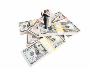 Photograph of bride and groom figurines dancing on top of stacks of U.S. paper currency, suggesting the idea of an expensive wedding.