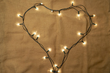 Heart shape made of christmas lights on sackcloth background