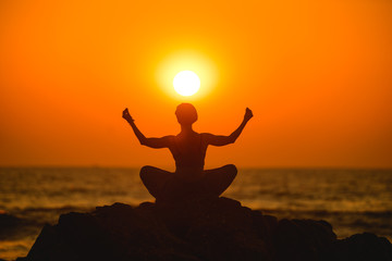 Female meditates during yoga in the sunset