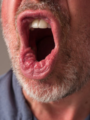 Close up photograph of a man's mouth yelling angrily with pursed lips.