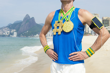 Hashtag gold medal athlete wearing mobile phone technology armband stands listening to motivational music outdoors on Ipanema Beach Rio de Janeiro Brazil