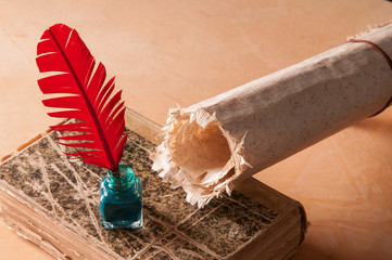 Red quill pen and a rolled papyrus sheet on an old book