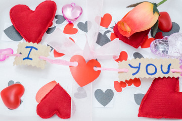 many hearts of different colors and shapes and a pink ribbon on a white background