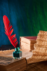 Red quill pen and a papyrus sheet and old books in a blue and green background