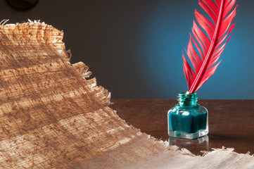 Red quill pen and a papyrus sheet on a wooden table in a blue background