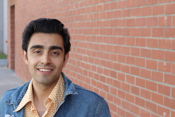 Close up portrait of Arabic nice man on the background of red brick wall with copy space on the right side.