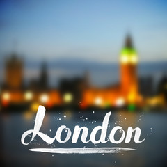 White calligraphy London sign on blurred photo background
