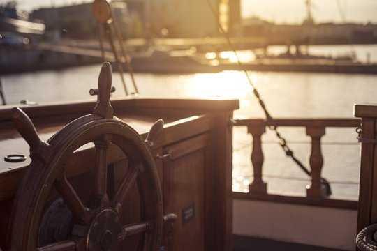 Steering wheel of an old wooden sailing ship in a port at sunset