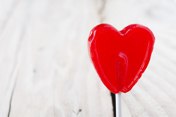 Valentine day concept - heart shaped lolly pop on wood backgroun