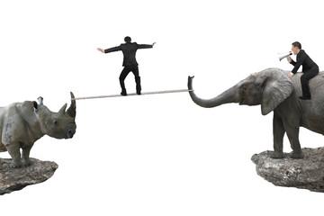 Obraz Man riding elephant against rhinoceros with another balancing ro - fototapety do salonu
