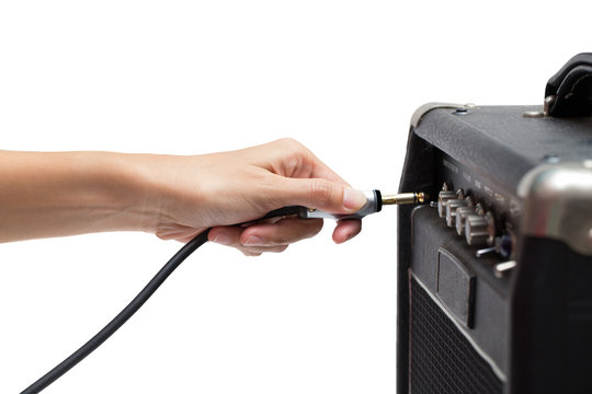 woman hand plugging into the amplifier guitar on white backgroun