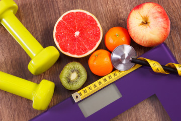 Electronic bathroom scale, centimeter and stethoscope, fresh fruits, dumbbells for fitness, slimming and healthy lifestyles concept