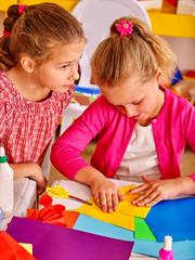 Portrait of group kids craft colored paper  in kindergarten .
