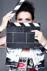 Brunette woman with blue eyes looking through a clapperboard.