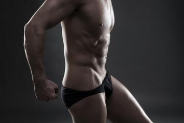 Handsome muscular bodybuilder posing on gray background. Low key studio shot