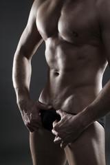 Handsome muscular bodybuilder posing on gray background. Low key close up studio shot