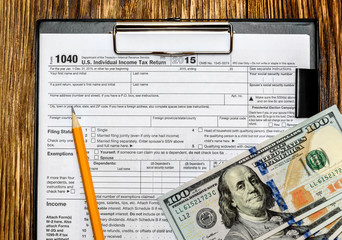 Tax form with pencil and US dollars on clipboard
