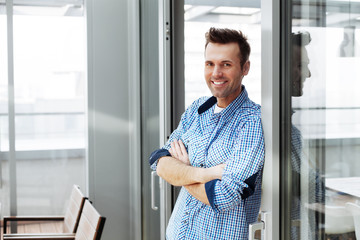 Freelancer taking a break. Young smiling adult standing next to a sliding glass door