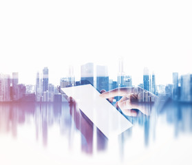 Female hand touching screen of her phablet, blurred city background. Double exposure.