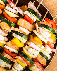 Skewers with chicken, becon and vegetables prepared for barbecue