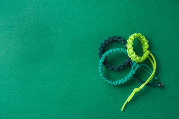 Three simple green paracord bracelets placed on a green grainy p