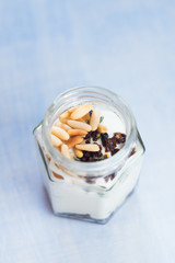 Greek yogurt with roasted pine nuts,  marinated dried tomatoes and thyme in jar. Healthy snack. Selective focus.