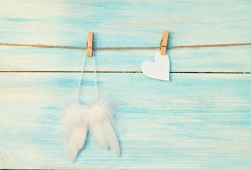 White soft angel's wings and paper heart pinned on wooden light turquoise background.