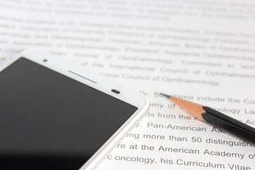 スマートフォンと英文と鉛筆