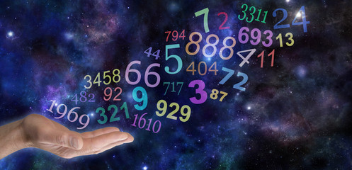 What do your Numbers mean - male hand palm up with a group   of random multicolored transparent numbers floating up and away on a wide deep space background with copy space