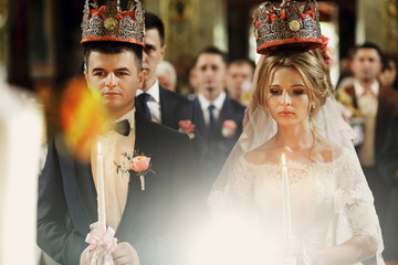 Religious blonde bride and handsome groom in crowns in church at