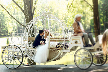 Handsome groom kissing blonde beautiful bride in magical fairy t