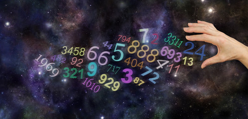The Universal Significance of Numbers - female hand about to take number 24 amongst a group of scattered multicolored transparent numbers on a wide deep space background with copy space