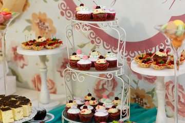 Delicious and tasty wedding dessert table with cupcakes and pies